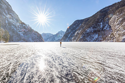 Germany, Berchtesgadener Land, back view of woman with backpack standing on frozen Lake Koenigssee - p300m1505391 by Michael Malorny