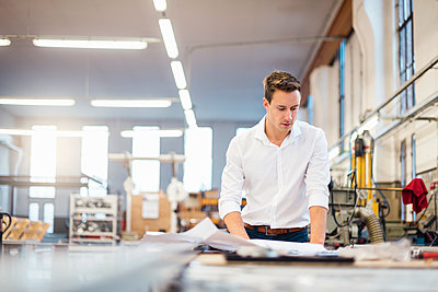 Young businessman in factory working on plan - p300m1562957 by Daniel Ingold