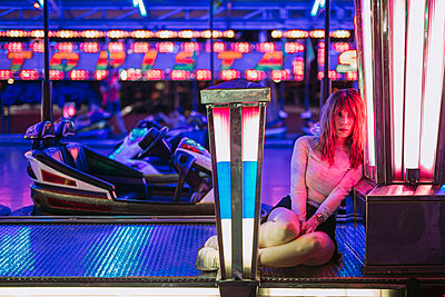 Young woman sitting at the bumper car on a funfair at night - p300m2132133 by DREAMSTOCK1982
