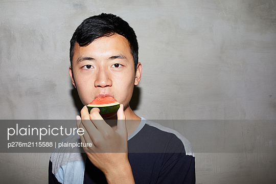 Young man bites into a piece of melon - p276m2115588 by plainpicture
