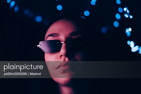 Portrait of confident young woman wearing sunglasses at illuminated restaurant - p426m2205268 by Maskot