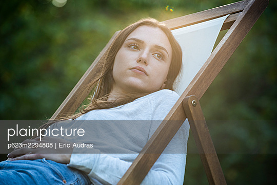 Thoughtful young woman with hands on stomach leaning on chair - p623m2294808 by Eric Audras