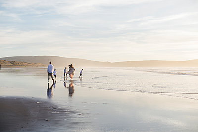 Rear view of family running on the sand during sunset at the beach - p1166m2073868 by Cavan Images