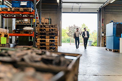 Male professional discussing with manager while walking at entrance of manufacturing factory - p300m2225349 by Daniel Ingold