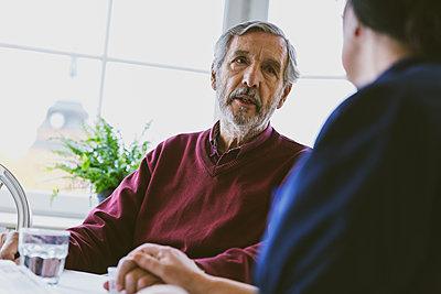 Senior man talking to female caretaker at home - p426m1468230 by Maskot