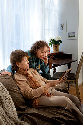 Hispanic mother and daughter admiring picture frame - p555m1408856 by Shestock