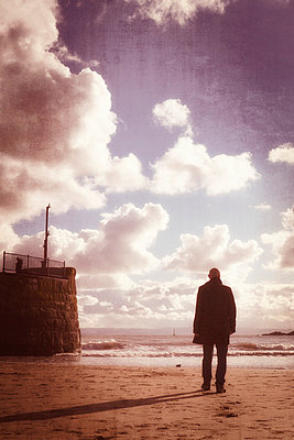 man in coat walking across harbour at low tide - p597m793868 by Tim Robinson