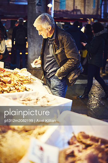 Man with banknote at a market stall with mussels - p1312m2082199 by Axel Killian