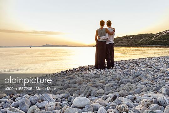 Greece, Pelion, couple enjoying at sunset at beach - p300m1587205 von Maria Maar