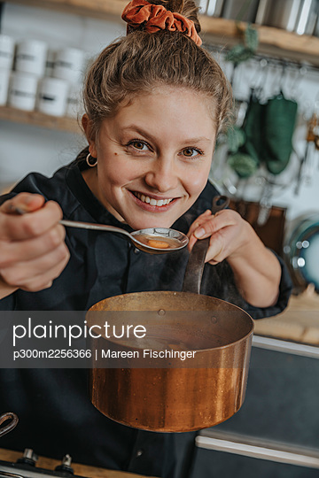 Smiling chef tasting broth soup in saucepan while standing in kitchen - p300m2256366 by Mareen Fischinger