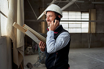 Smiling male building contractor talking over smart phone inside construction site - p300m2244190 by Veam