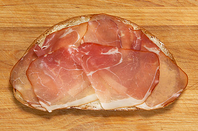 Slice of bread with raw ham, elevated view - p300m879499 by Tom Hoenig