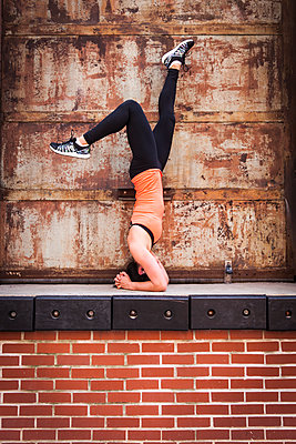 Woman Doing Exercise On Top Of Brick Wall - p343m1218170 by Lucie Wicker