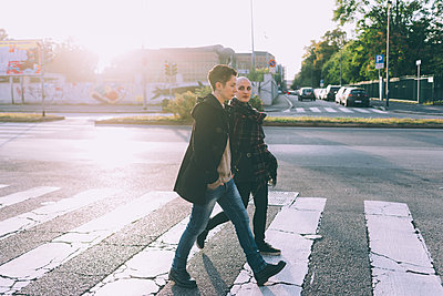 Young lesbian couple walking across pelican crossing city street - p429m1206984 by Eugenio Marongiu