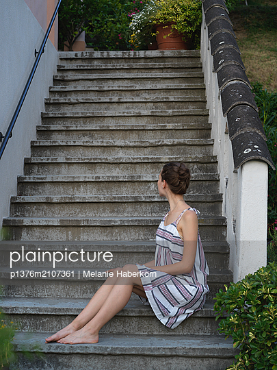 Young woman sitting on stone steps - p1376m2107361 by Melanie Haberkorn