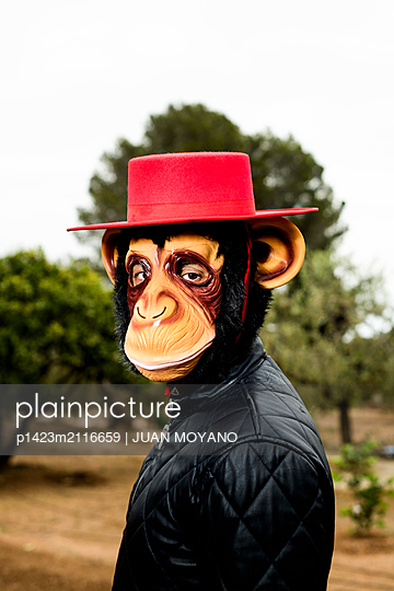 Man with a monkey mask and a Spanish hat in a natural landscape - p1423m2116659 by JUAN MOYANO