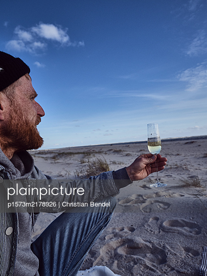 Man with champagne glass on the beach - p1573m2178926 by Christian Bendel
