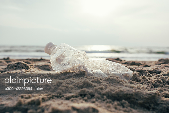 Plastic water bottle on sand at beach - p300m2226394 by alev