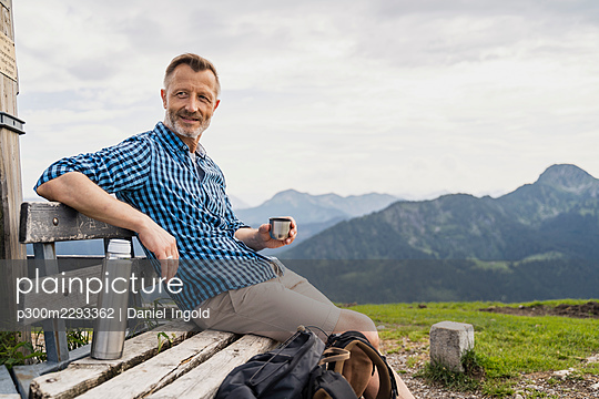 Man holding coffee while sitting on bench - p300m2293362 by Daniel Ingold