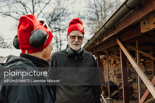 Senior man in front of wood shed - p312m2190973 by Jennifer Nilsson