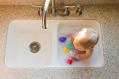 High angle view of baby boy with toys sitting in kitchen sink - p1166m1543955 by Cavan Images