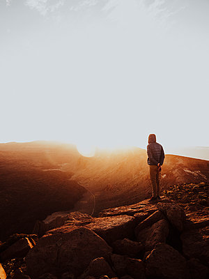 Man standing on top of a mountain watching sunrise - p1166m2129898 by Cavan Images