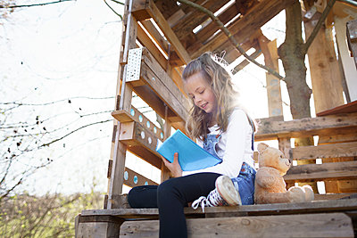 pretty young girl sits in the garden in front of the tree house and writes something in her blue notebook, diary during the corona quarantine, lower austria - p300m2180238 von Epiximages