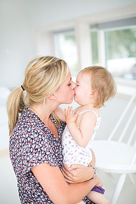Mother kissing her daughter - p312m765543f by Anna Roström