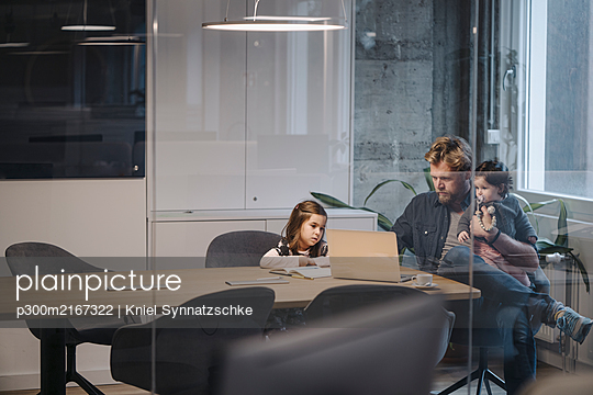 Casual businessman with two daughters working at desk in office - p300m2167322 by Kniel Synnatzschke