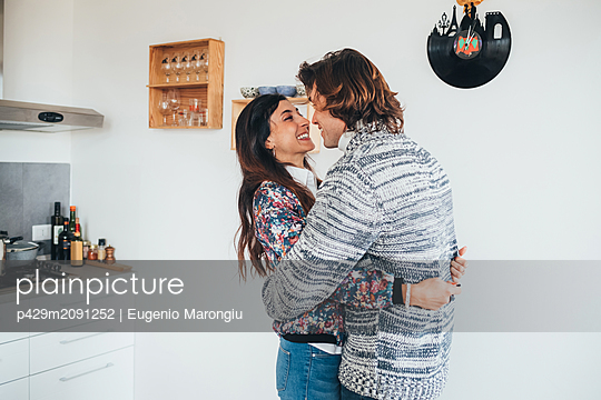 Couple hugging in kitchen - p429m2091252 by Eugenio Marongiu