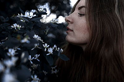 Caucasian woman smelling flowers outdoors - p555m1232055 by Vyacheslav Chistyakov