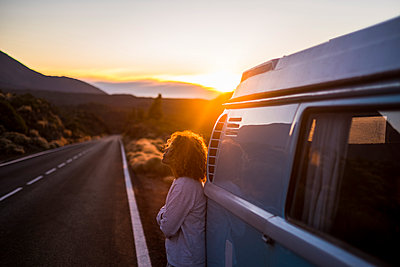 Spain, Tenerife, pensive woman at sunset leaning against van parked at roadside - p300m1505887 by Simona Pilolla