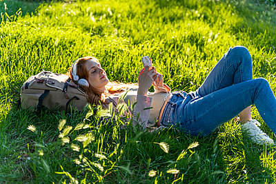 Young redheaded woman with headphones and smartphone in a park - p300m2113796 von VITTA GALLERY
