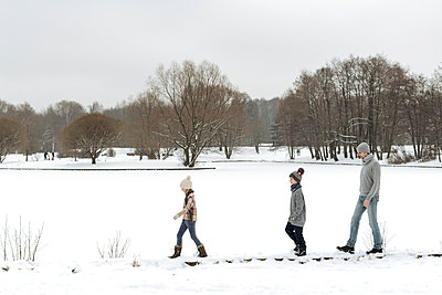 Father and two children walking in winter landscape - p300m2166438 by Ekaterina Yakunina