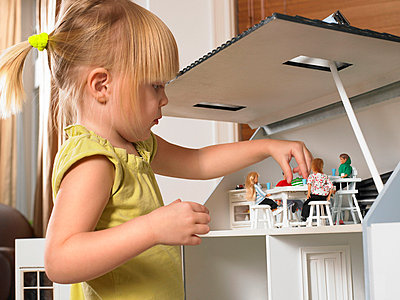 Little girl playing with a doll house - p4292517f by Ghislain & Marie David de Lossy