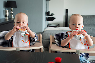 Baby twin brothers drinking juice in high chairs - p429m1022607 by Attia-Fotografie