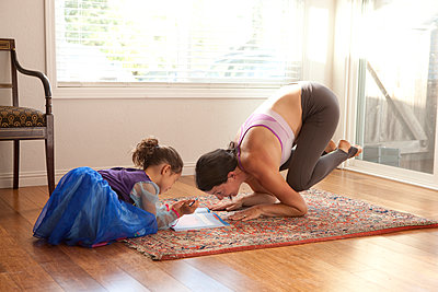 Woman practicing yoga and helping daughter with homework - p555m1408828 by Shestock