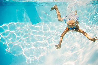 Caucasian boy swimming underwater in pool - p555m1421660 by JGI/Jamie Grill