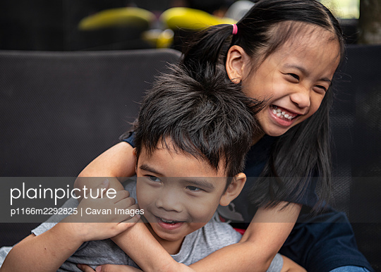 picture of two young Thai siblings playfully embrace - p1166m2292825 by Cavan Images