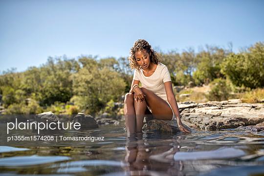 Junge Frau badet ihre Füße im Fluss - p1355m1574208 von Tomasrodriguez