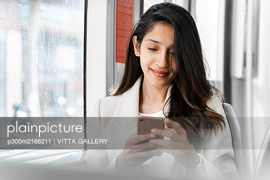 Young woman using smartphone in a tram - p300m2166211 by VITTA GALLERY