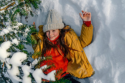 Smiling girl in yellow jacket lying on snow under tree during winter - p300m2267827 by Oxana Guryanova