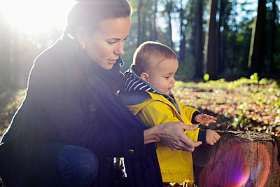 Mother and young toddler looking at tree stump - p429m898254 by Attia-Fotografie