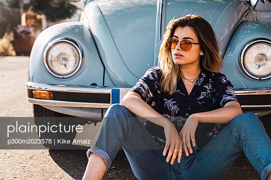 Young woman wearing sunglasses sitting outside at a vintage car - p300m2023578 von Kike Arnaiz