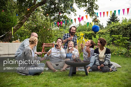 Freunde im Schrebergarten rösten Marshmallows - p788m1165257 von Lisa Krechting