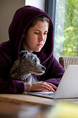 Young woman working on laptop at home, stay at home due to Covid-19 - p1057m2185214 by Stephen Shepherd