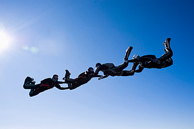 Four people holding hands and flying - p31226173 by Hans Berggren