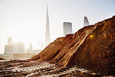 Pile of dirt at building site, Dubai skyscraper on background - p312m1024859f by Magnus Ragnvid