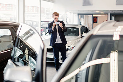 Man photographing car through smart phone at dealership store - p426m1036565f by Maskot