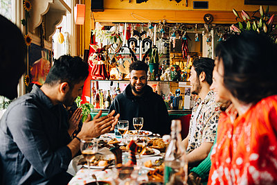 Cheerful young multi-ethnic friends enjoying brunch while sitting at table in restaurant - p426m2046342 by Maskot